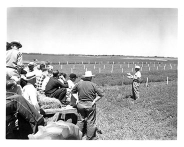 UMN professor speaks to farmers on a hayrack at a field day